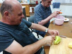Na fotografiji dvije osobe, jedna osoba čisti papriku, a druga mrkvu.