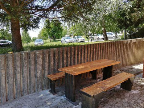 Uređen vanjski prostor Udruge. Na fotografiji drveni stol i dvije klupe, u hladu bora.