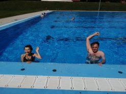 Na fotografiji su dvije osobe u bazenu, mašu i pozdravljaju