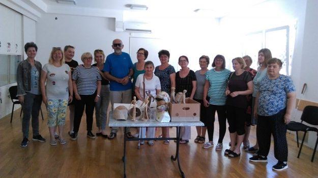 Konferencija Mreže slijepih žena u Premanturi, na fotografiji je velika skupina žena, ispred njih je stol s proizvodima s kreativnih radionica
