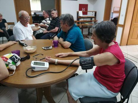 Kontrola zdravstvenog stanja, na fotografiji skupina ljudi sjedi za dva stola, u prvom planu je žena koja mjeri razinu krvnog tlaka