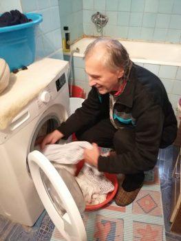 Na fotografiji je muškarac, vadi rublje iz perilice rublja.