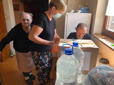 Na fotografiji se nalaze starija muška i ženska osoba, koje preuzimaju paket od mlađe ženske osobe i potpisuju potpisnu listu.