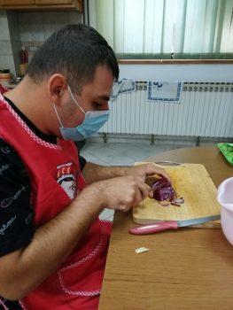 Na fotografiji se nalazi mlađa muška osoba koja sjecka ljubičasti luk na kulinarskoj radionici.
