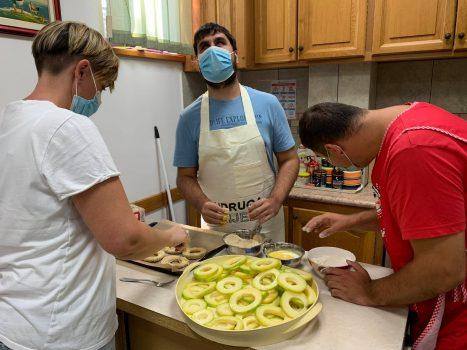 Na fotografiji se nalaze dvije muške i jedna ženska osoba koje zajednički pripremaju tikvice za pohanje.