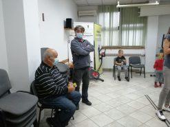 Na dotografiji su dva muškarca, jedan sjedi na stolici, a drugi muškarac  stoji kraj njega