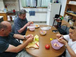 Na fotografiji tri osobe čiste povrće.