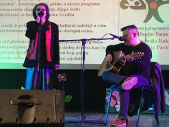Na fotografiji žena stoji iza mikrofona, muškarac svira gitaru.