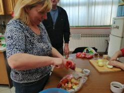 Na fotografiji ženska osoba čisti povrće.