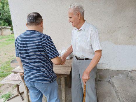 Na fotografiji se nalaze dvije muške osobe koje se rukuju i razgovaraju pored kuće.