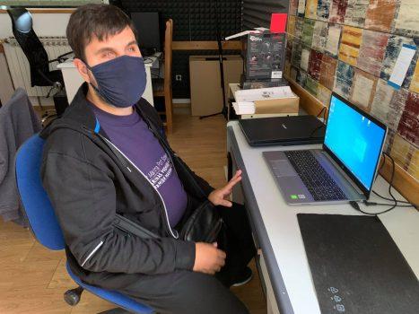 Na fotografiji se nalazi mlađa muška osoba koja sjedi pored laptopa.