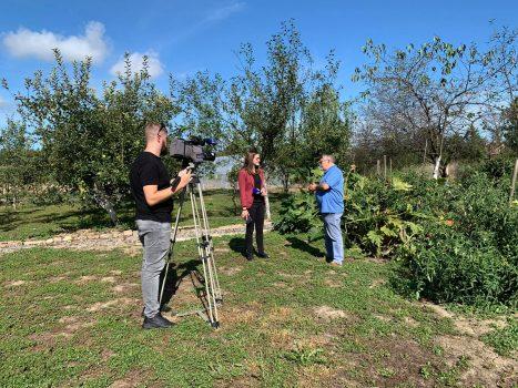 Na fotografiji se nalazi televizijska ekipa koja snima mušku osobu pored povišenih vrtnih gredica.
