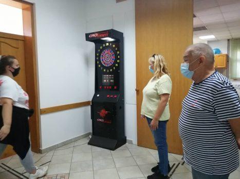 Na fotografiji se nalaze jedna mlađa ženska osoba i dvije starije muška i ženska osoba koji igraju pikado