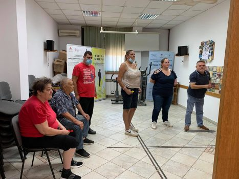 Na fotografiji se nalazi skupina ljudi, muška i ženska osoba igraju pikado