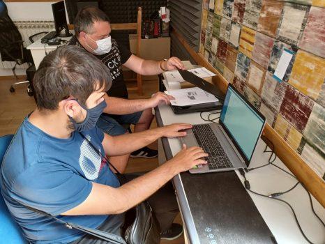 Na fotografiji su dvije muške osobe.Jedan muškarac koristi prijenosno računalo, a drugi koristi skener.